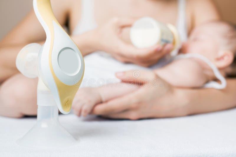 Handborstpomp met melk, moeder en baby bij achtergrond royalty-vrije stock afbeeldingen