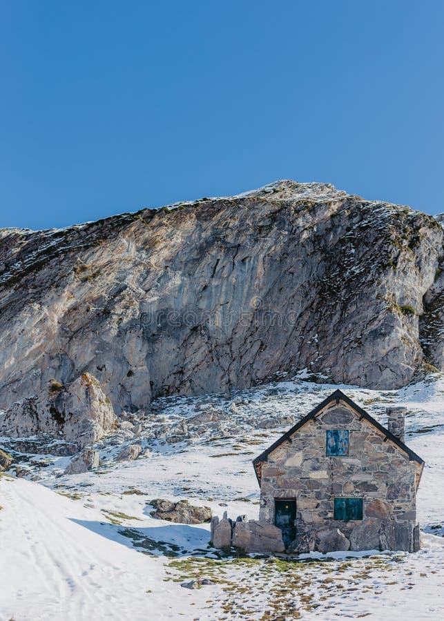 Handbuilt серый каменный дом с высокими утесами и красивым ясным голубым небом на заднем плане стоковые изображения rf