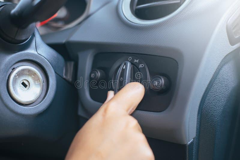 Handchauffören vänder på den ljusa strömbrytaren i bil royaltyfri foto