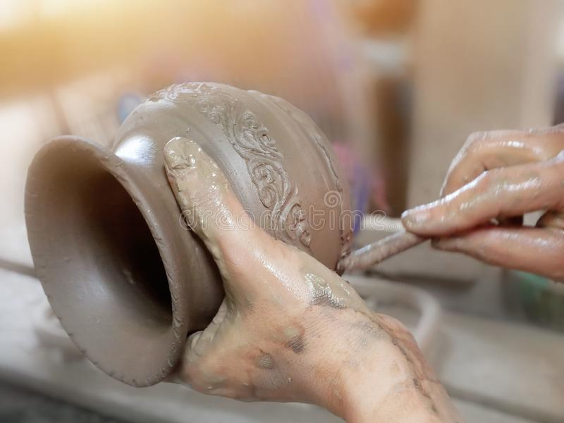 Handcraft artist making pattern on earthenware pottery stock images