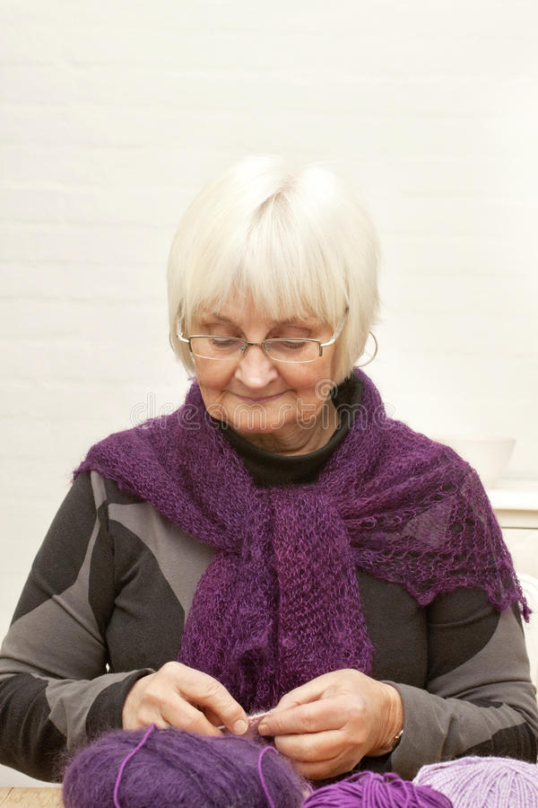 Handcraft - Old woman knitting stock photography
