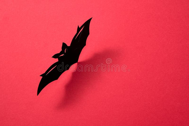 Handcraft paper bat on a red background with shadow and copy space for text. Layout to Halloween. Flat lay. Paper flying handcraft bat presented on a red stock photography