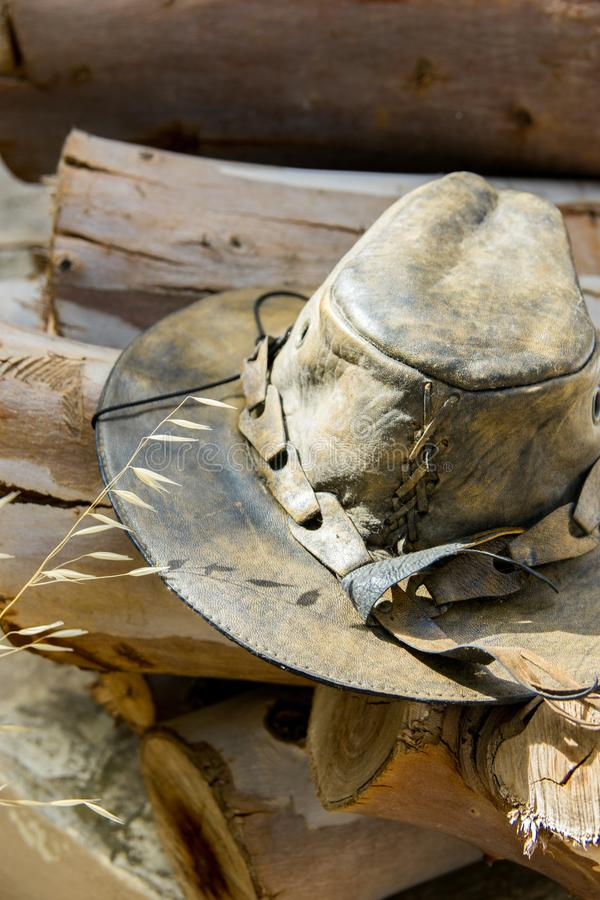 Handcrafted artisan old leather hat lying on wood logs in forest prepared for making fire.. Hiking camping wanderlust royalty free stock image