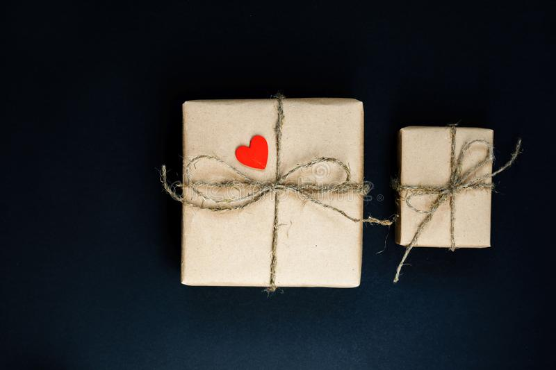 Handcrafted gift box wrapped in Craft paper with red wooden heart, rope and bow on black background. Top view, flat lay royalty free stock photos