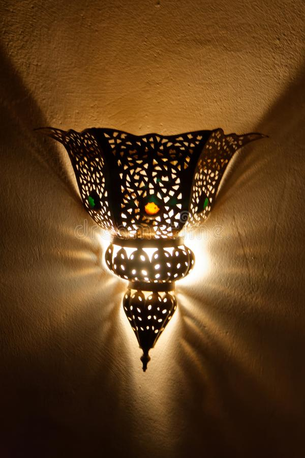 Handcrafted Moroccan lamp. On hotel wall, with a kind of devilish aspect stock image