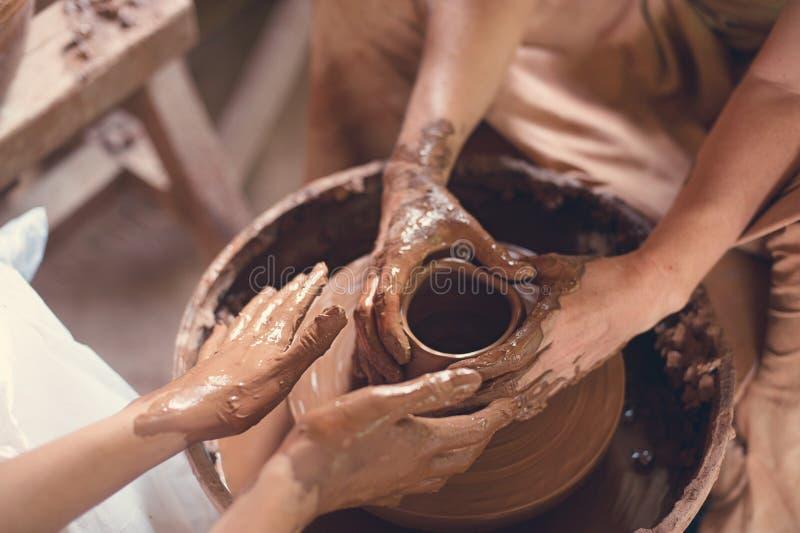 Handcrafted på ett hjul för keramiker` s, gör händer lera från olika objekt för hem och försäljning i lagret och på utställningen royaltyfria foton