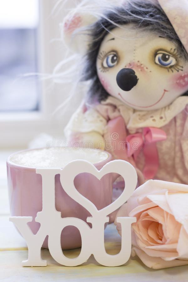 A handcrafted toy, a cup of coffe and a rose stock photos
