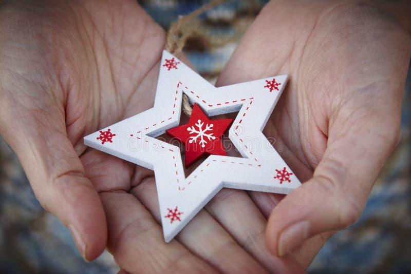 Handcrafted wooden christmas stars. Tenderness between elderly people. Horizontal. Handcrafted wooden christmas stars. Love and tenderness between elderly people stock images