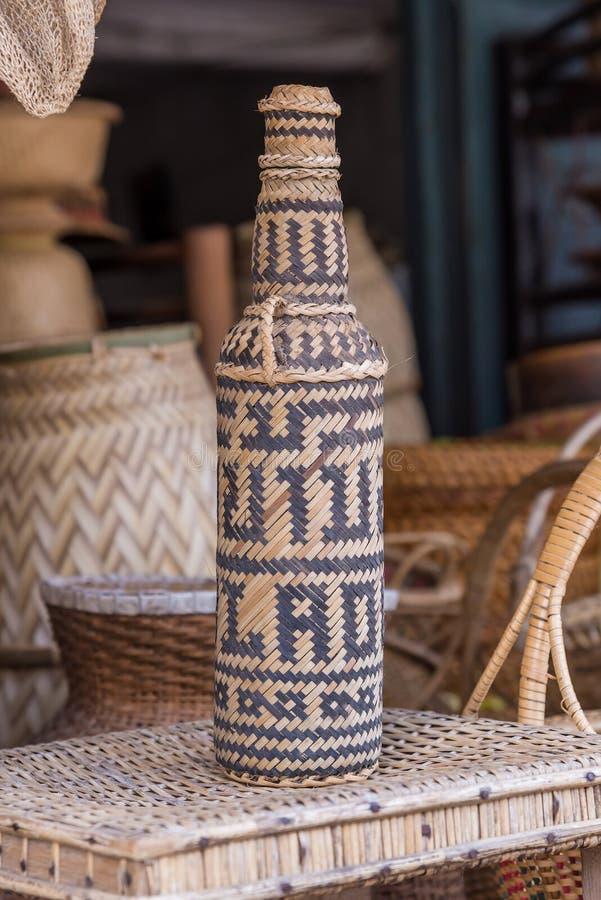 handcrafts täckande glasflaskor av rottingväv royaltyfri foto