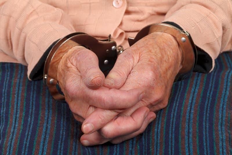Handcuffed elderly woman stock photos