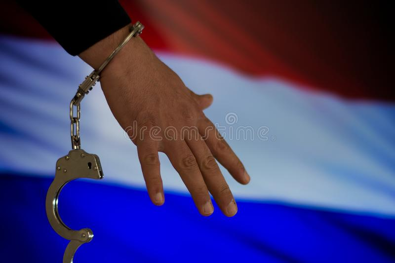 Handcuffed hand in front of the country flag. crime concept royalty free stock photo