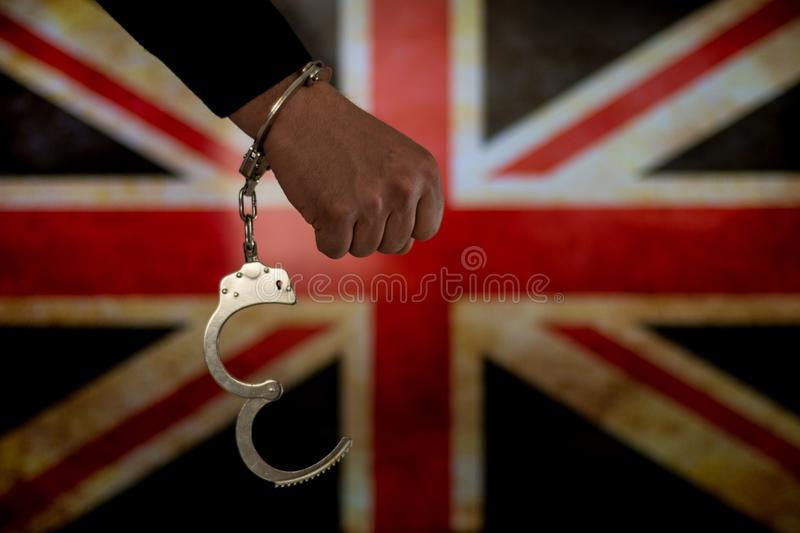 Handcuffed hand in front of the country flag. crime concept stock images