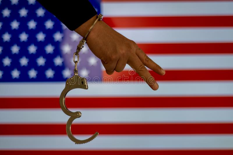 Handcuffed hand in front of the country flag. crime concept royalty free stock image