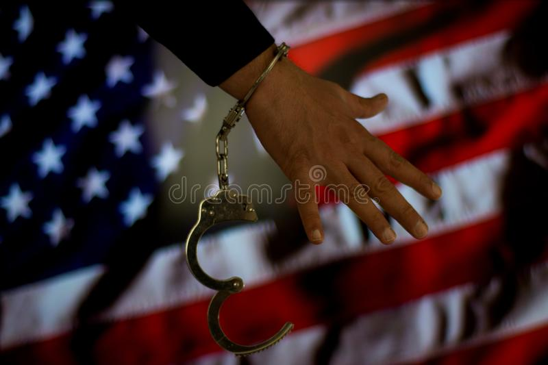 Handcuffed hand in front of the country flag. crime concept stock photos