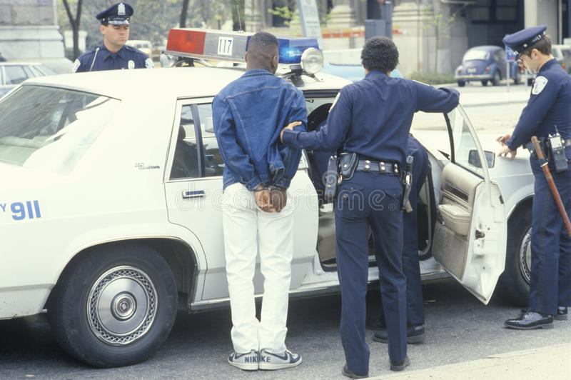Handcuffed man being put into police car royalty free stock photos