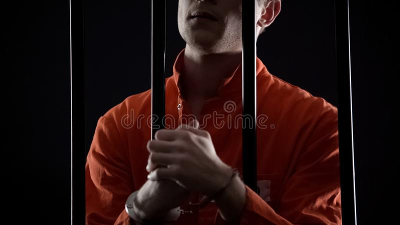 Handcuffed prisoner eagerly waiting for appeal court verdict, feeling nervous. Stock photo royalty free stock image
