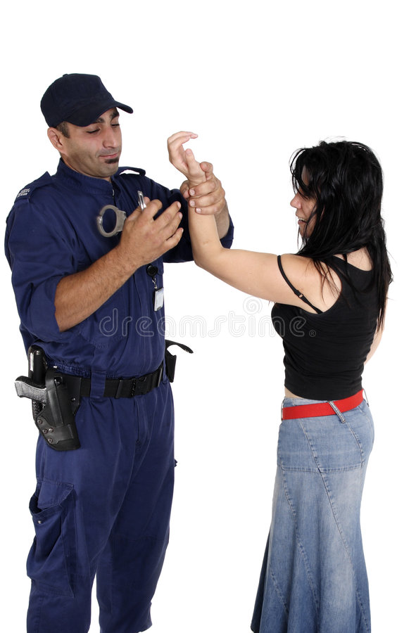 Handcuffing a ciminal. A male security officer handcuffs a female. Cuffs show motion royalty free stock photos