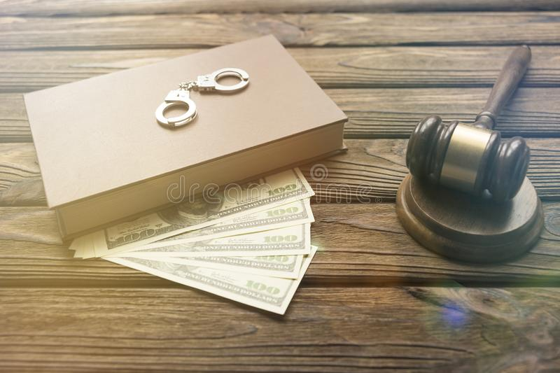 Handcuffs, book, dollars, hammer of a judge. On a wooden background. jurisprudence. court stock photos