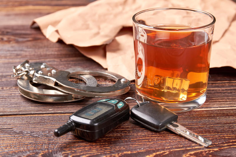 Handcuffs, car keys, whisky glass. Glass of alcohol, metal handcuffs, keys close up. Driver and alcohol is big irresponsibility stock photo