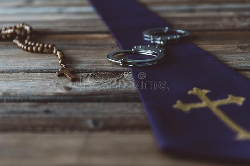 Handcuffs and catholic church symbols. Church and crime stock image