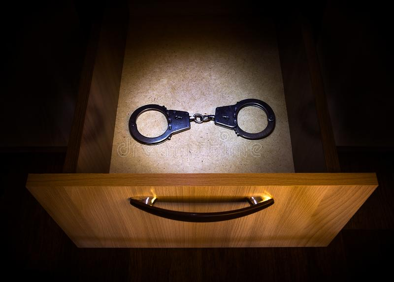 Handcuffs in the Drawer. Handcuffs in the Opened Drawer of the Furniture in the Dark Room royalty free stock photo