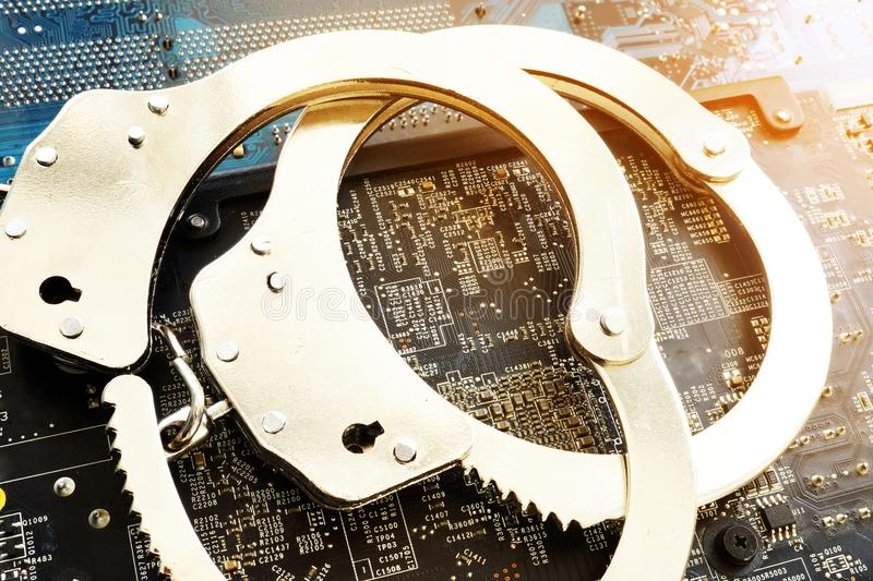 Handcuffs and electronic devices. Cyber crime or fraud. stock image