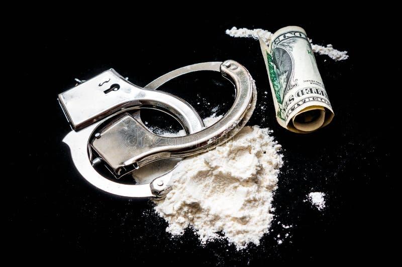 Handcuffs, geld en drugs op zwarte achtergrond stock foto
