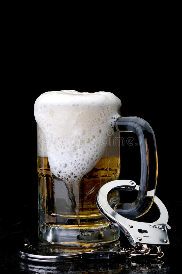 Handcuffs on the handle of a beer mug. Vertical image of handcuffs on the handle of a beer mug : alcoholism royalty free stock images