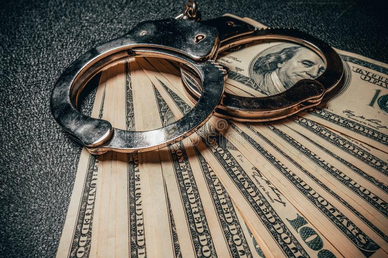 Handcuffs on hundred dollar american banknotes on black background. The concept of corruption, robbery, fraud. Close-up.  stock image