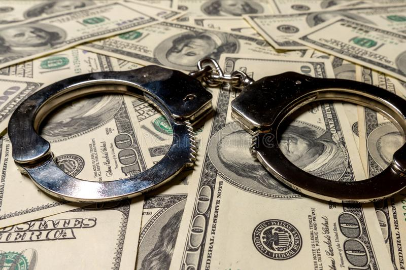 Handcuffs on hundred dollar american banknotes. The concept of corruption, robbery, fraud. Close-up. Handcuffs on hundred dollar american banknotes. The concept royalty free stock image