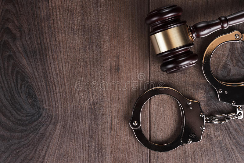 Handcuffs and judge gavel on wooden background stock image