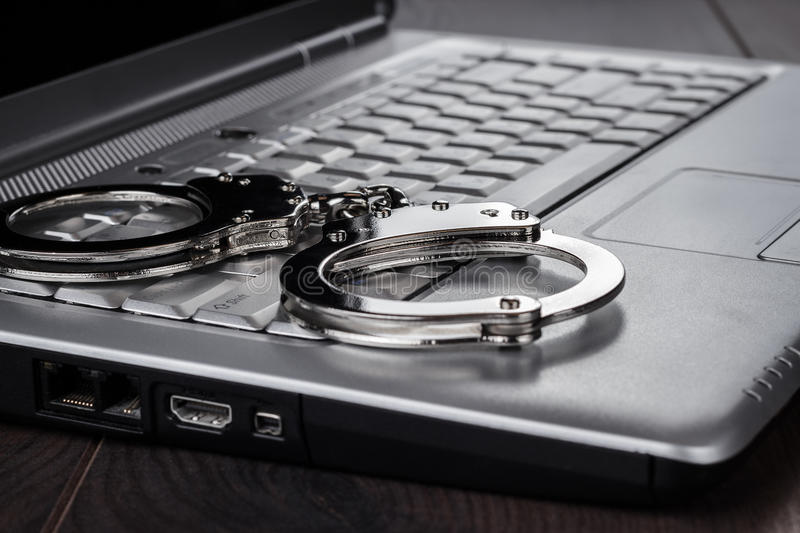 Handcuffs on laptop cyber crime concept stock photography