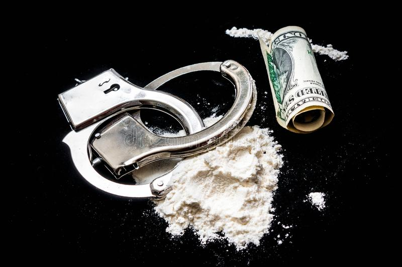 Handcuffs, money and drugs on black background stock photo