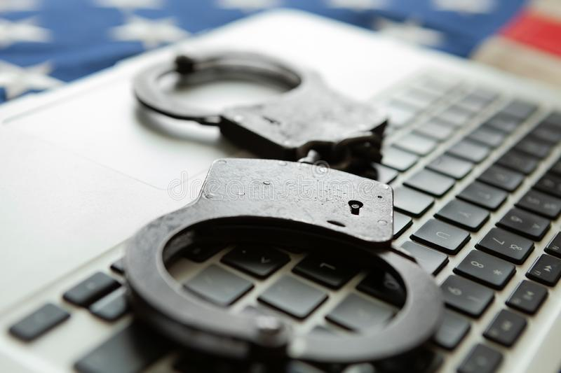 Handcuffs over a laptop with an old USA flag on background - close up studio shot stock images