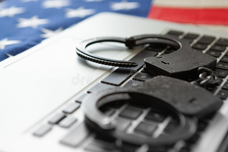 Handcuffs over a laptop with USA flag on background - close up studio shot royalty free stock photography