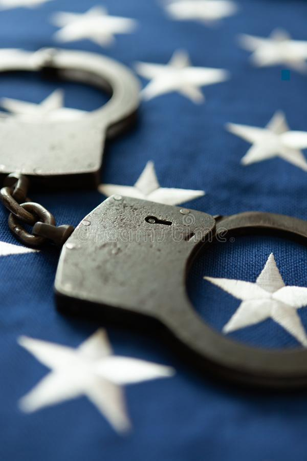 Handcuffs over an old rustic USA flag - close up studio shot royalty free stock image