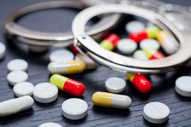 Handcuffs and pills and drugs on wooden table stock image