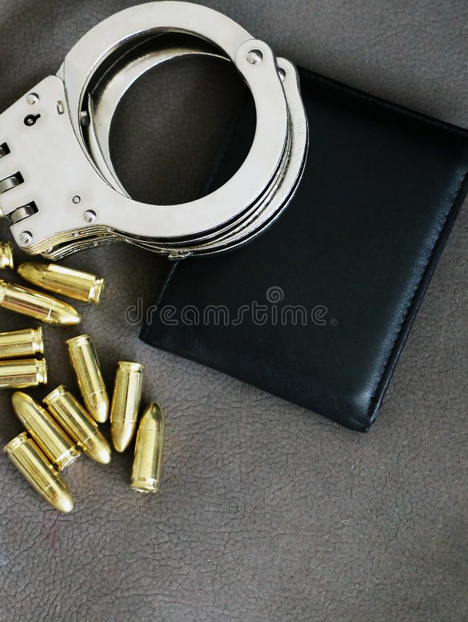 Handcuffs, pistol bullets and ID holder for cops, special forces and defense units equipment. Close up background royalty free stock images