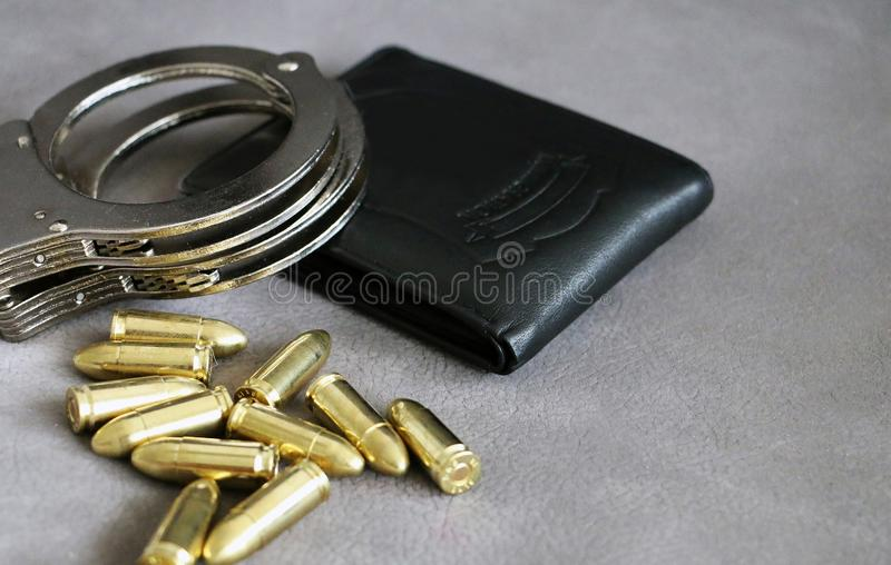 Handcuffs, pistol bullets and ID holder for cops, special forces and defense units equipment. Close up background stock photos