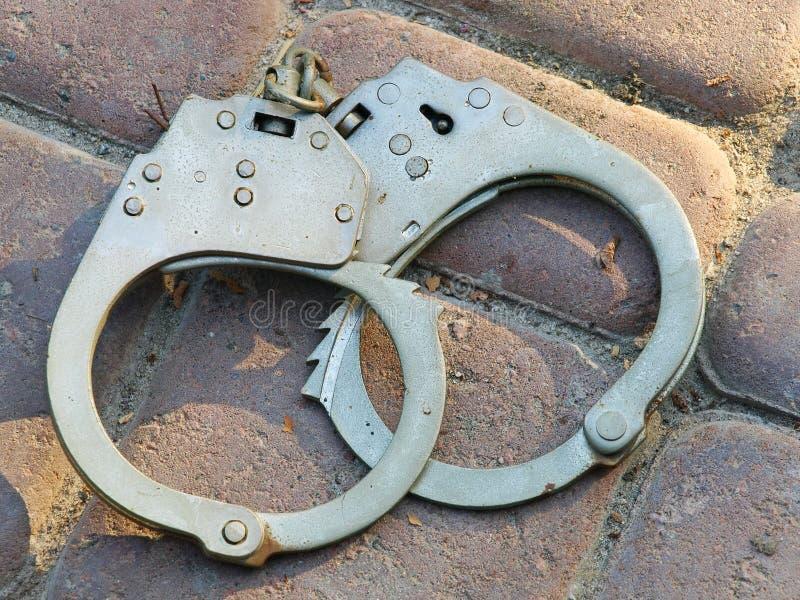 Handcuffs on a stone floor tiles. stock photos