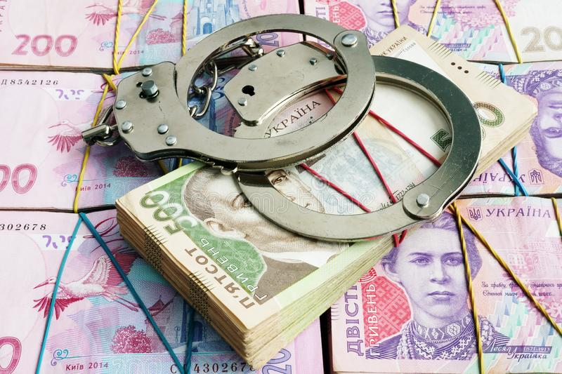 Handcuffs on Ukrainian currency hryvnia. Corruption and financial crime or penalty. Concept stock image