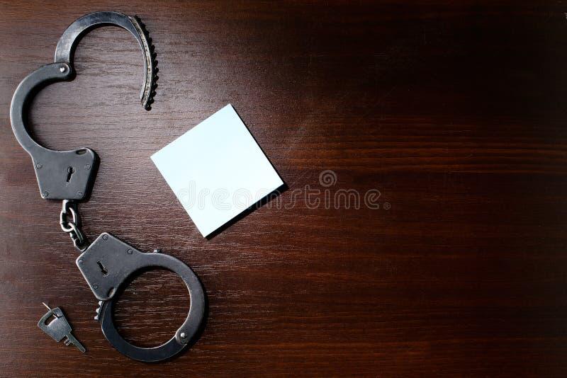 Handcuffs van de staalpolitie en leeg blad van document kader voor yo royalty-vrije stock foto
