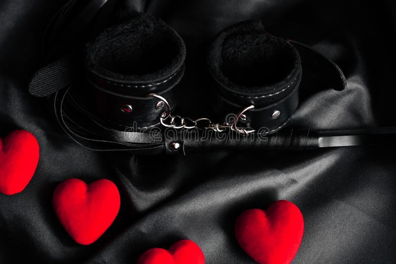 Handcuffs and whip for BDSM sex with red hearts. stock photography