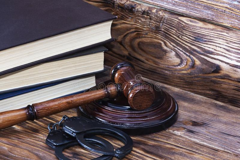 Handcuffs and a wooden gavel in front of manila folders stock photos