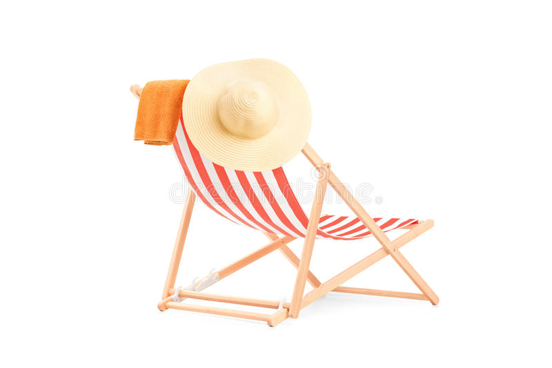 Handdoek en hoed op een zonlanterfanter met strepen stock foto
