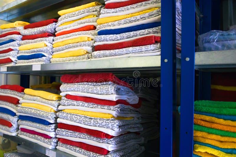 Handdoeken, bedbladen en kleren op de plank stock foto