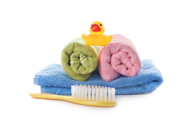 Handdoeken en borstel en stuk speelgoed op witte achtergrond royalty-vrije stock afbeeldingen