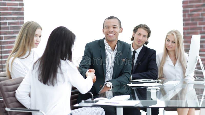 Handdruk bedrijfsvrouwen met partner bij de het onderhandelen lijst royalty-vrije stock afbeeldingen