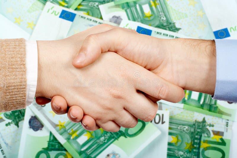 Handdruk en geld stock foto