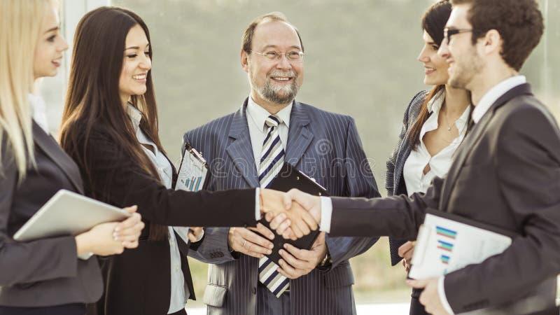 Handdruk financiële partners, en procureurs van het bedrijf op de achtergrond van het bureau stock afbeelding